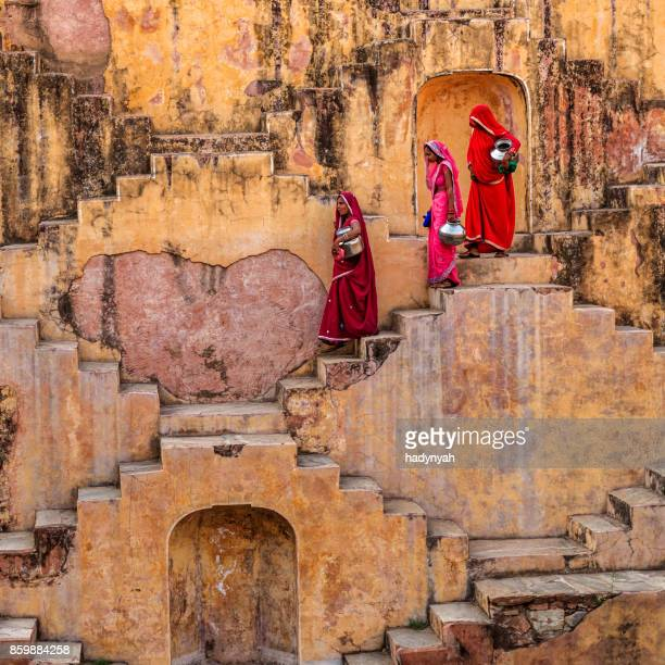 indian women carrying water from stepwell near jaipur - stepwell stock photos and pictures