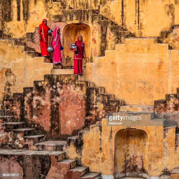 indian women carrying water from stepwell near jaipur - stepwell india stock photos and pictures