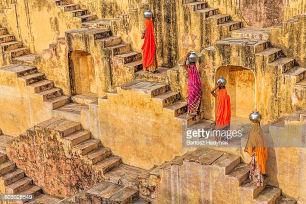 indian women carrying water from stepwell - stepwell stock pictures, royalty-free photos & images