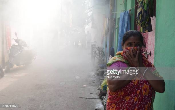 Indian Women cover their faces as a municipal worker fumigates a slum area to prevent the spread of dengue fever and other mosquitoborne diseases in...