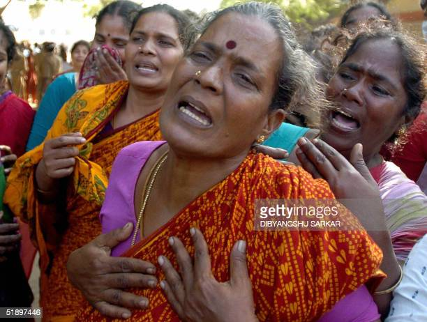 Indian women cry after seeing the dead body of a relative at a mortuary in Cuddalore some 185 kms southwest of Madras 28 December 2004 The death toll...