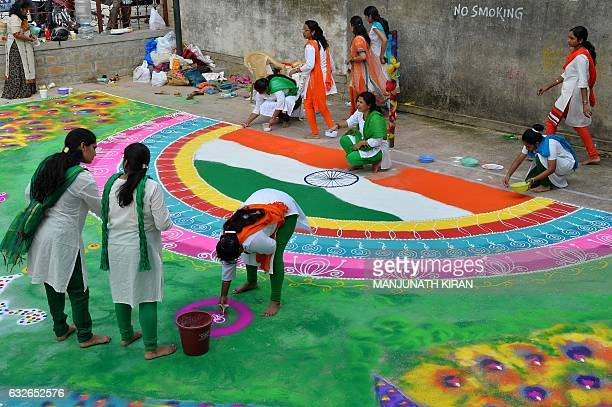 Indian women draw a 'rangoli' with the Indian national flag on the eve of the 68th Indian Republic Day celebrations in Bangalore on January 25 2017...