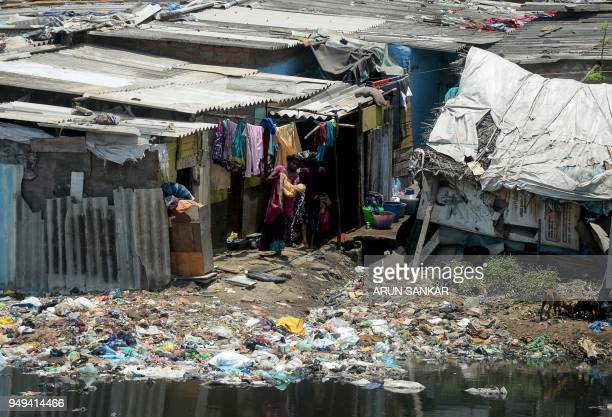 Indian women dries washed clothes near the polluted Cooum River next to homes in Chennai on April 21 2018 April 22 is observed as Earth Day every...