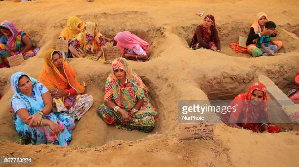 Indian women farmers with bodies buried till neck in pits stage ' Zameen Satyagrah' protest against forced acquisition of their land by Jaipur...