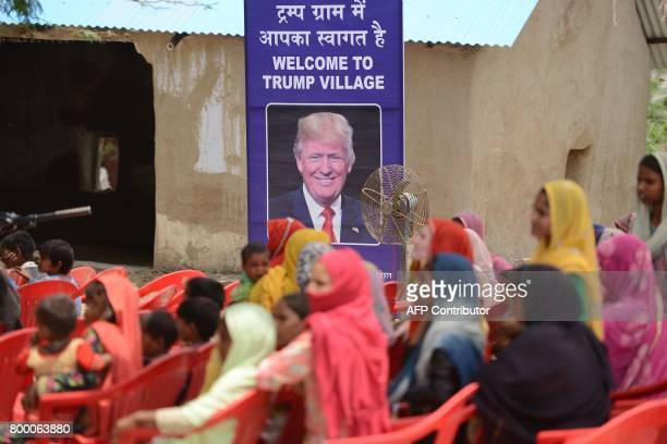 Indian women gather to listen to a speaker next to a poster with the image of US President Donald Trump during a ceremony at Marora village which has...