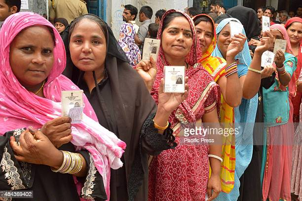Indian women give their votes for the civic body poll during the municipal election at the municipal corporation election