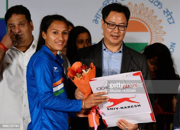 Indian women hockey team captain Rani Rampal receives a bouquet of flowers from Union Minister of State for Home Affairs of India Kiren Rijiju during...