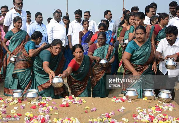 Indian women leave pots of milk as offerings during a ceremony for the victims of the 2004 earthquake and tsunami at Marina Beach in Chennai on...