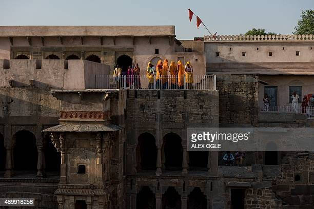 Indian women look over historic Chand Baori stepwell in Abhaneri village in Rajasthan on September 24, 2015. For a few hours on one day each year...