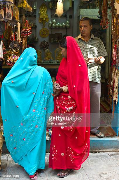 Indian women looking in shop window of jewellery shop in the city of Varanasi Benares Northern India