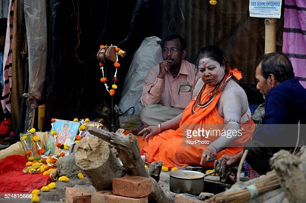 Indian Women Naga Sadhu on his way to the annual holy dip at Gangasagar gestures towards a visitor as he rests at a transit camp in Kolkata India