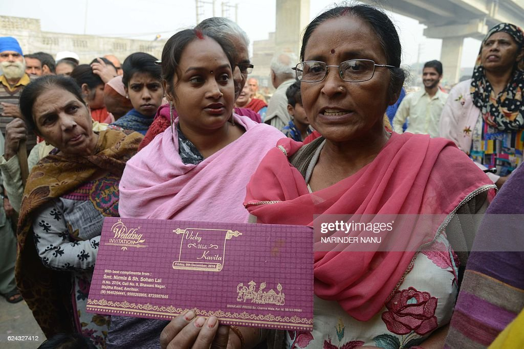 Indian women Nirmla stands in a queue outside bank as she holds her son`s wedding invitation card in hopes of withdrawing money for the event in...