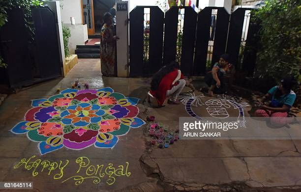 Indian women paint a traditional 'Kolam' at their residence in Madurai on 14 January 2017 some 450km southeast of Chennai People paint traditional...