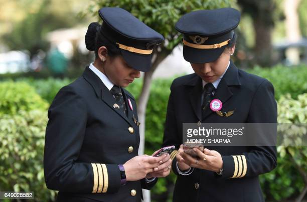 Indian women pilots from Air India look at their mobile phones during an event on the eve of International Women's Day in New Delhi on March 7 2017 A...