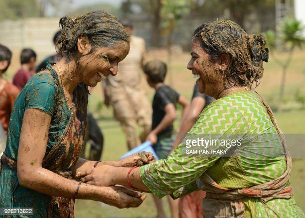 TOPSHOT Indian women play with fresh cow dung mixed with cow urine and leaves from the butea tree as they celebrate the Holi festival at the Bansi...