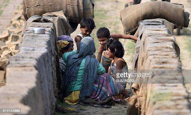 TOPSHOT Indian women play with their children after finishing work at a brick factory on the eve of International Workers' Day at Chandrapur near...