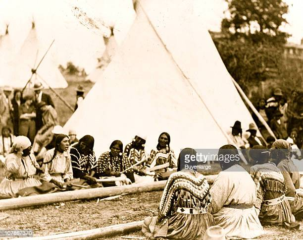 Indian women playing the stick game at the midsummer celebration on the Glacier National Park Reservation Montana 1925