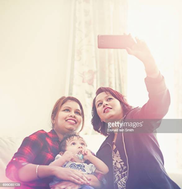 Indian women posing for cell phone selfie with baby boy