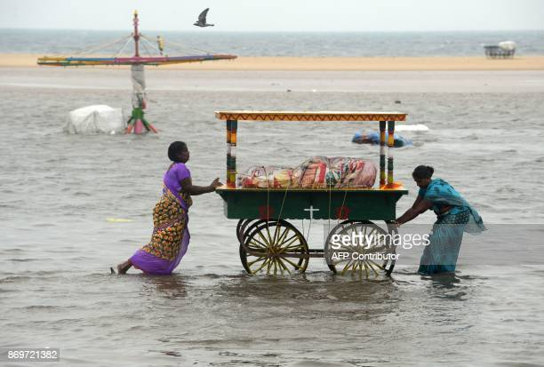 Indian women push a food cart stall through flood waters at Marina Beach on the Bay of Bengal coast after heavy rain in Chennai on November 3 2017...