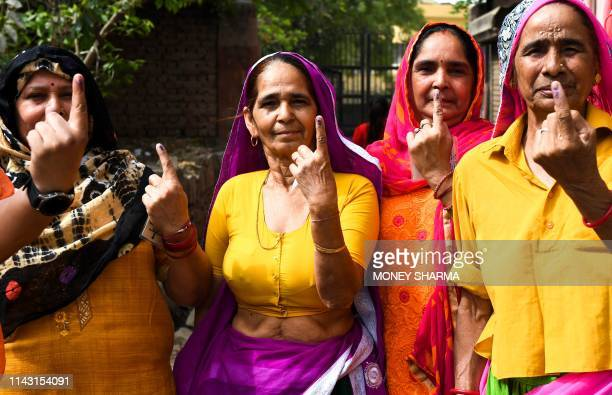 Indian women show their inkmarked finger after casting their vote at a polling station in Gurgaon in the northern Indian state of Haryana on May 12...