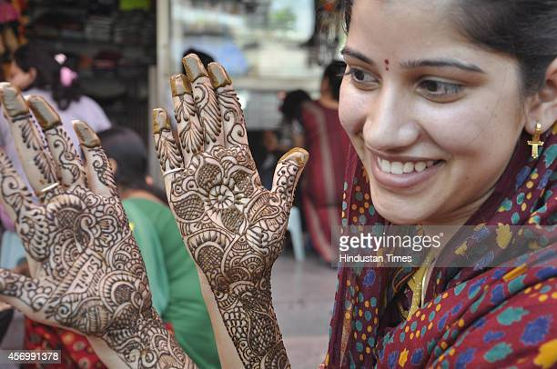 Indian women show their palms and arms decorated with mehandi or henna on the eve of Hindu festival of Karva Chauth in Raj Nagar on October 10 2014...