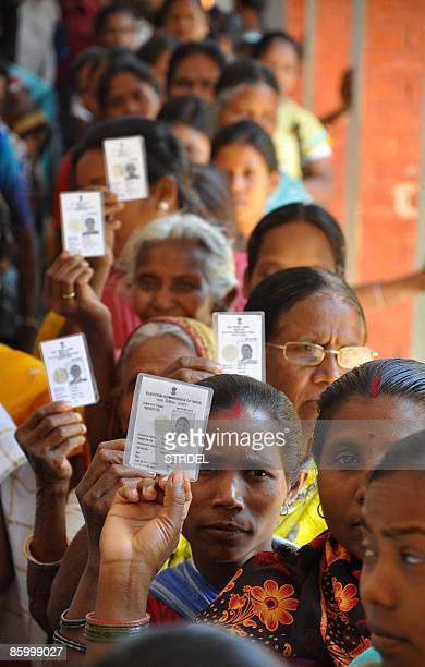 Indian women show their voter identity cards to photographers as they queue to cast their votes at a polling station in Khunti on April 16 in the...