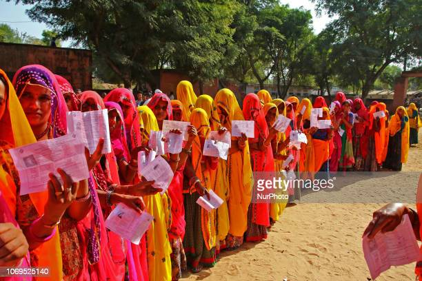 Indian women shows their identity cards as they queue to cast their vote at a local polling station for the state Assembly elections at Raisar...