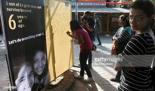 Indian women sign a board during Daughters' Day in New Delhi on September 22 2011 One in 13 girls do not survive beyond six years of age and an...