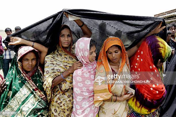Indian women stand in a queue to cast their votes at a booth of a panchayat repoll in Basanti some 100 Kms south of Kolkata on May 19 2008 At least...