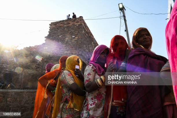 TOPSHOT Indian women stand in queue to cast their vote at a local polling station during Rajasthan's Legislative Assembly election in Jodhpur on...