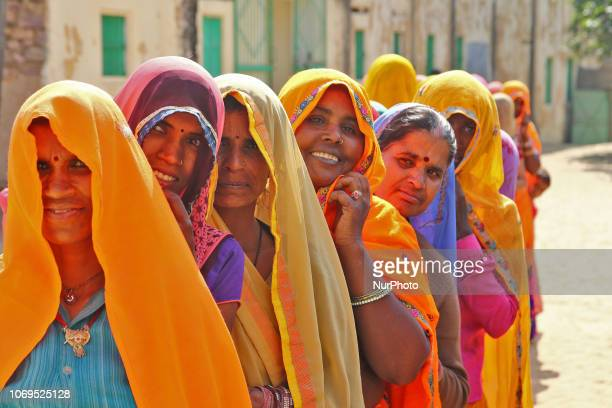 Indian women stand in queue to cast their vote at a local polling station for the state Assembly elections at Raisar Village of Jaipur District...
