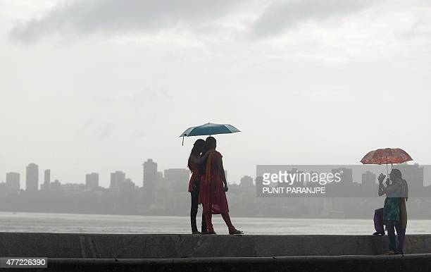 Indian women stroll pose for a photo near the seafront during rain showers in Mumbai on June 15 2015 AFP PHOTO/ PUNIT PARANJPE