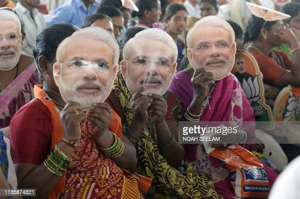Indian women supporting the Bharatiya Janata Party wears a mask of Prime Minister Narendra Modi at a rally held by party president Amit Shah ahead of...