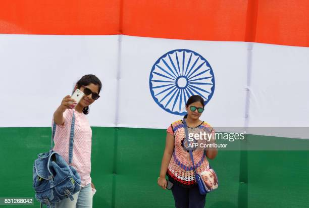 Indian women take a selfie in front of a large national flag at Sudha Cars Museum in Hyderabad on August 14 2017 Indian Independence Day is...