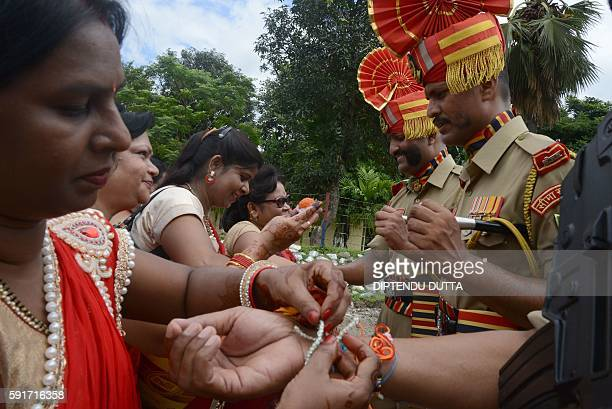 Indian women tie a 'rakhi' or sacred thread onto the wrist of an Indian Border Security Force personnel on the occasion of the Hindu festival Raksha...