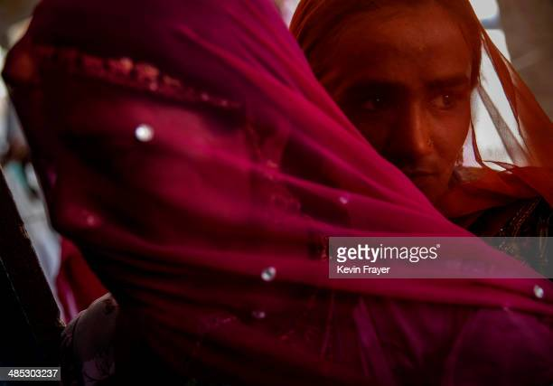 Indian women wait to vote at a polling station on April 17 2014 in the Jodhpur District in the desert state of Rajasthan India India is in the midst...
