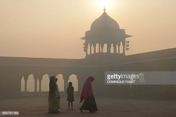 TOPSHOT Indian women walk as smog envelops the Jama Masjid Mosque in the old quarters of New Delhi on November 3 2016 India's capital with 18 million...