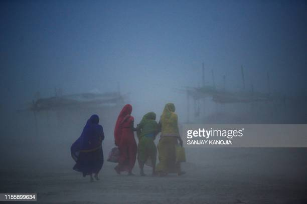 TOPSHOT Indian women walk during a dust storm at the Sangam the confluence of the rivers Ganges Yamuna and mythical Saraswati in Allahabad on July 16...