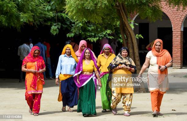 Indian women walk out after casting their vote at a polling station in Gurgaon, in the northern Indian state of Haryana on May 12 for the sixth phase...