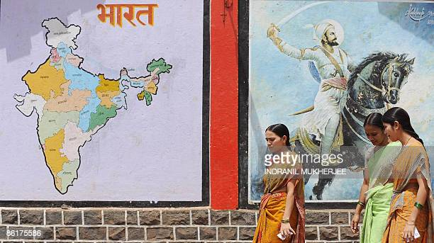Indian women walk past a political map of the country and an image of Maratha warrior king Chatrapati Shivaji painted on a school building wall after...