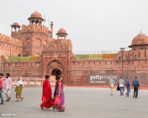 Indian women wearing colorful saris walk by the exterior red sandstone architecture of The Red Fort in Delhi, India.
