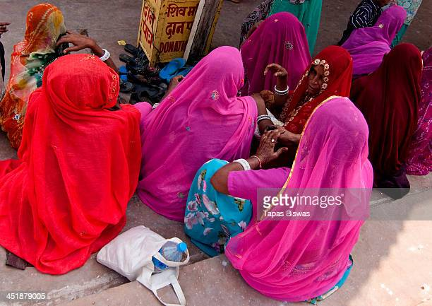 CONTENT] Indian women wearing colourful sarees are sitting together in a religious festival at Pushkar in Rajasthan India