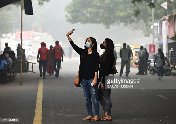 Indian women wearing protective masks take a selfie amid smog in New Delhi on November 6 2016 Schools in the Indian capital will be closed for the...