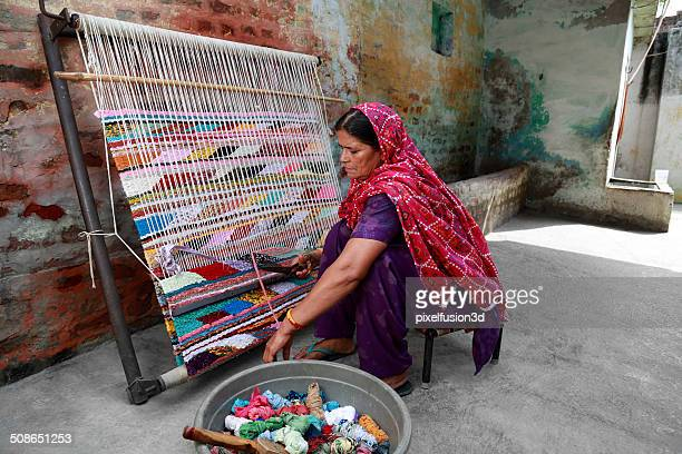 indian women weaving textile (durry) . - woven stock photos and pictures
