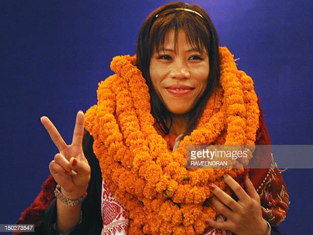 Indian women's boxing champion and Olympic Bronze medal winner Mary Kom wearing marigold garlands presented by wellwishers gestures during a...