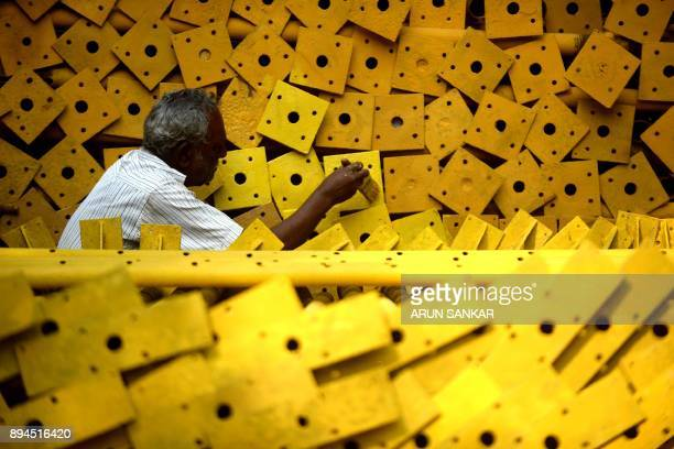 Indian worker Arumugam paints iron rod at an under construction site in Chennai on December 18 2017 SANKAR