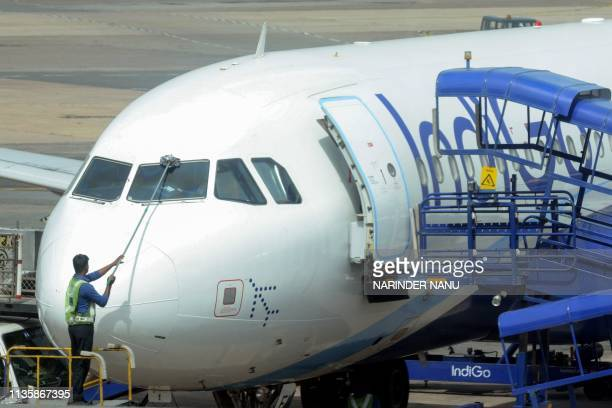 Indian worker cleans the front window of an IndiGo plane at Indira Gandhi International Airport in New Delhi on April 9 2019