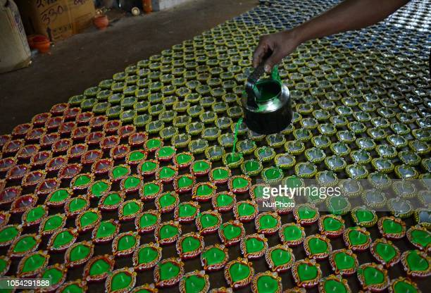 Indian worker filling wax on Diyas or Earthen Lamp at a workshop for the upcoming Diwali festival at the outskirts of Kolkata , India on Saturday ,...