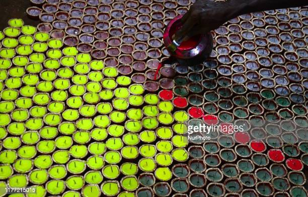Indian worker filling wax on Diyas or Earthen Lamp at a workshop for the upcoming Diwali festival at the outskirts of Kolkata , India on Sunday ,...