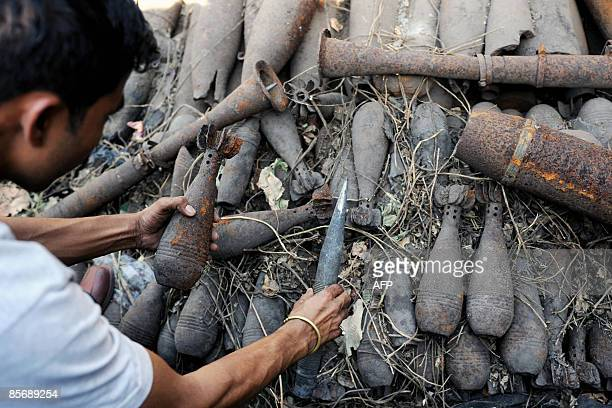 Indian worker handles scrapped munitions originating from Iraq at the Salasar steel furnace mill, where it was dumped four years ago by officials, at...